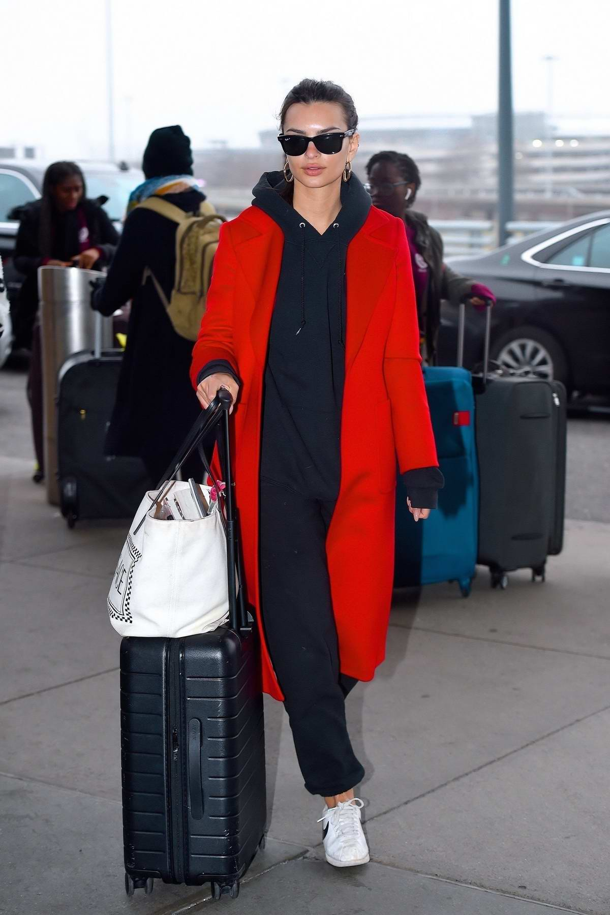 Emily Ratajkowski looks comfy yet stylish in a hoodie and bright red trench coat as she arrives at JFK airport in New York City