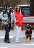 Emily Ratajkowski wears a bright red puffer jacket while out to walk her dog in New York City