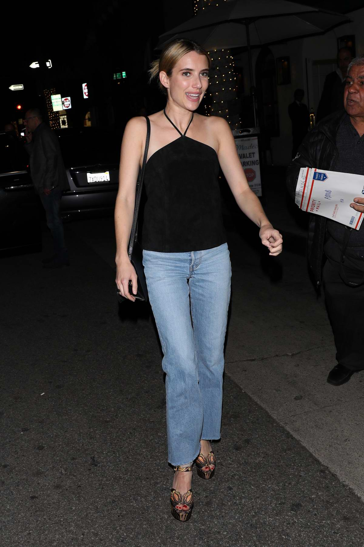 Emma Roberts seen wearing a black top and jeans while out for dinner at Madeo in Beverly Hills, California