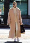 Hailey Bieber wears a beige long coat and Nike Air Force 1s as she steps out in Los Angeles