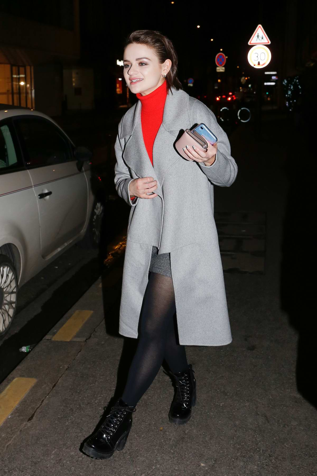 Joey King seen wearing a grey long coat and red turtleneck while out for a stroll in Paris, France