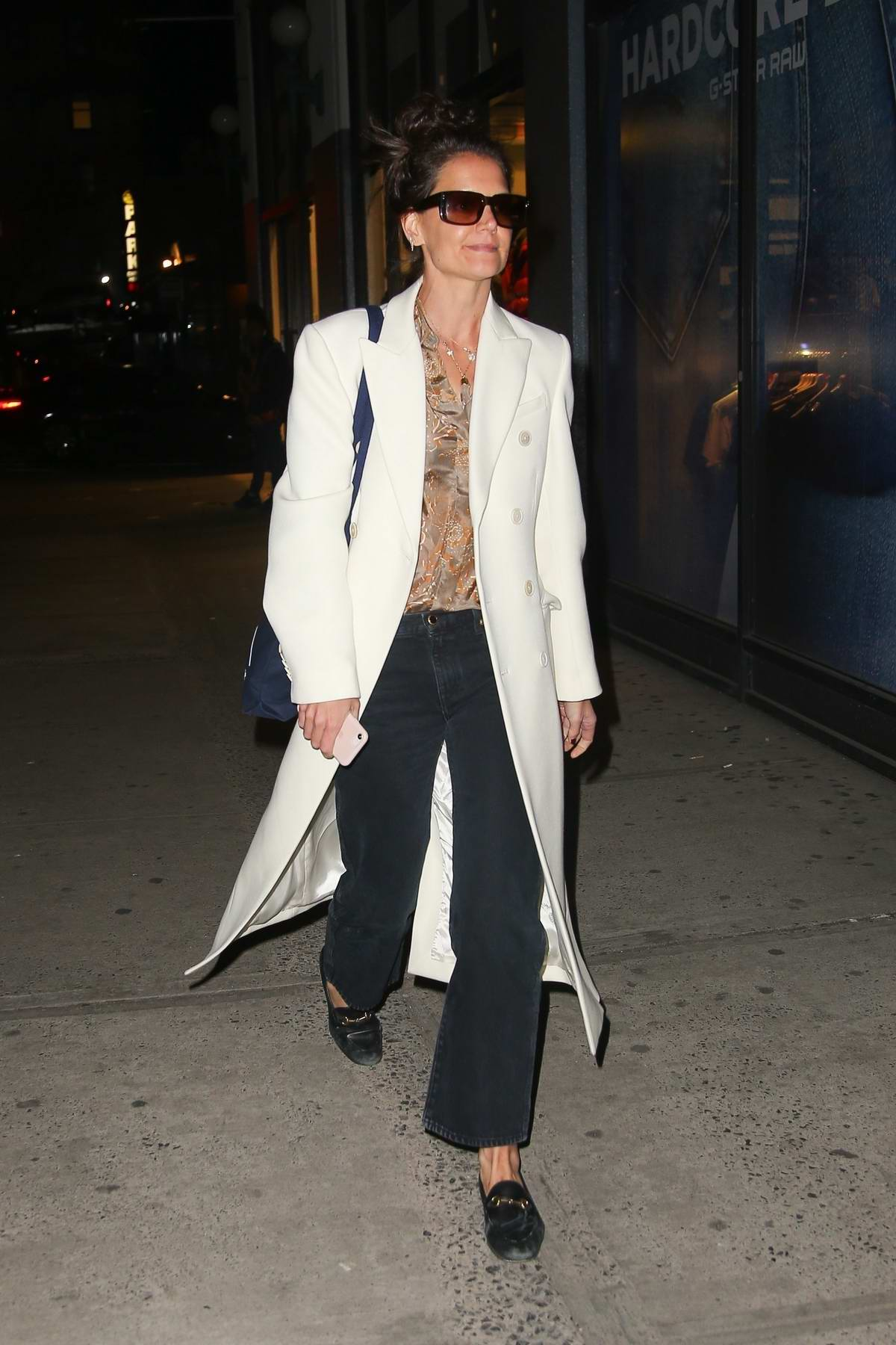 Katie Holmes wears a white long coat while out in New York City