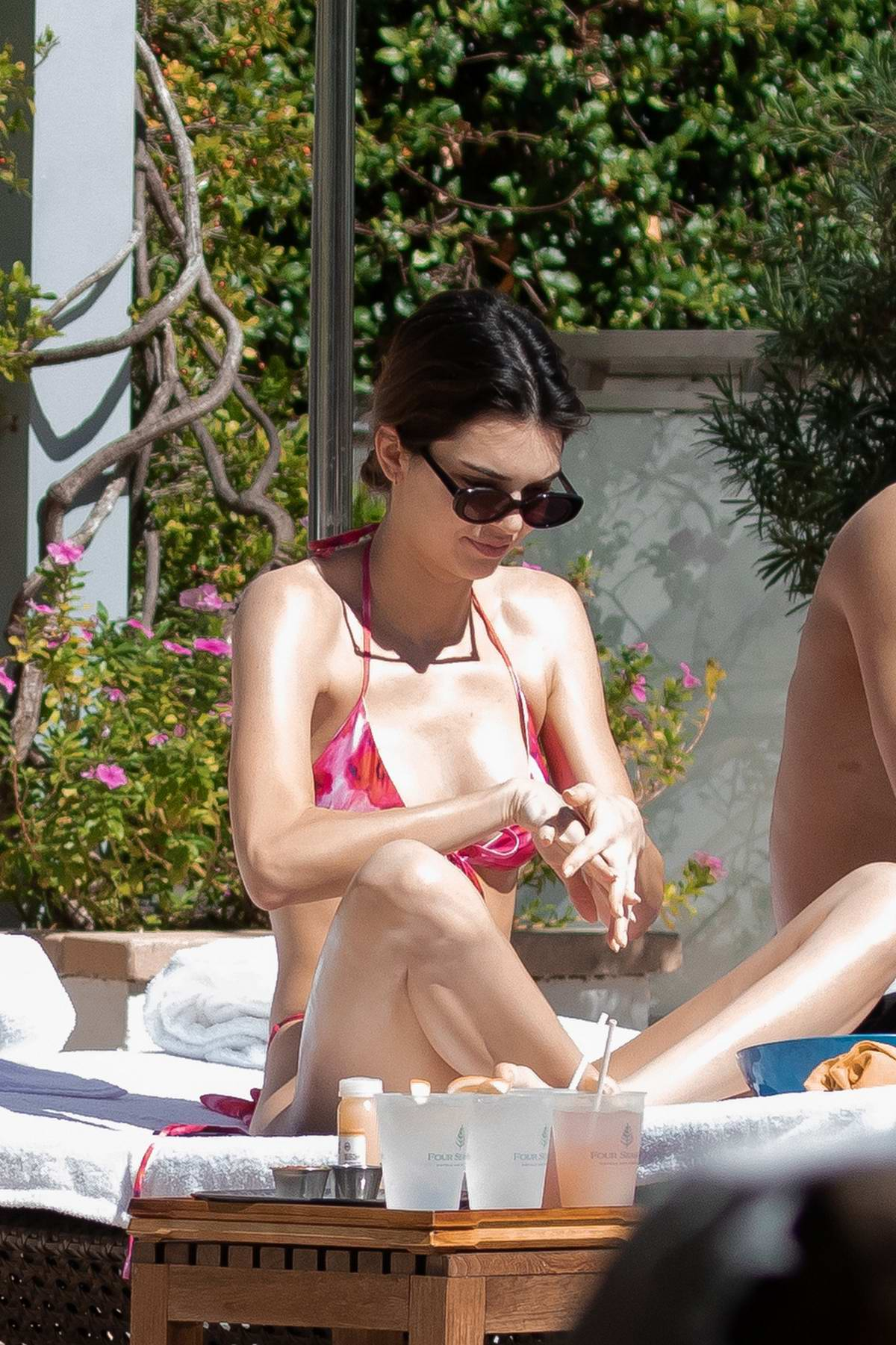 Kendall Jenner seen wearing a pink bikini while relaxing by the pool with Ben Simmons in Miami, Florida