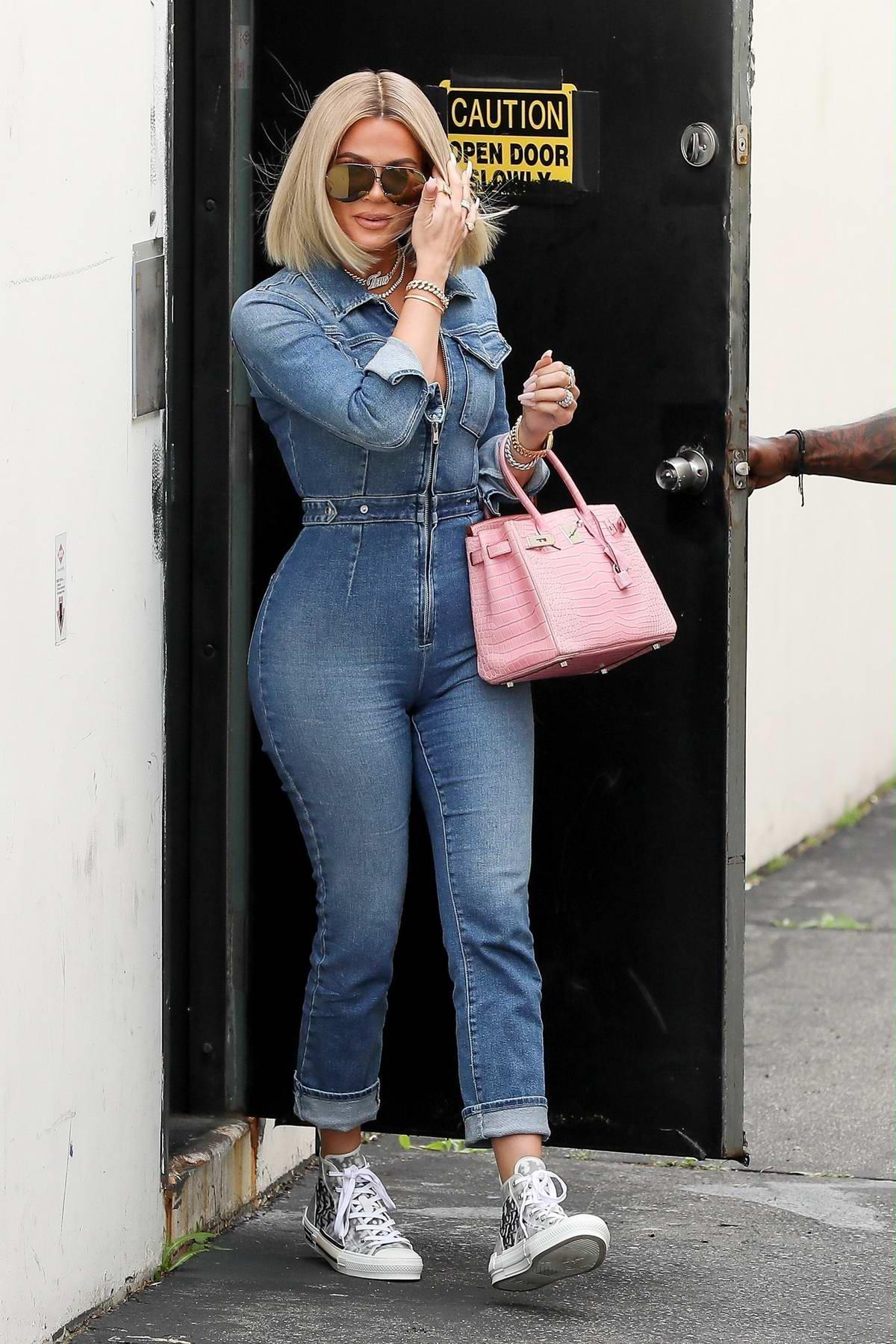 Khloe Kardashian flaunts her curves in a denim jumpsuit as she leaves a studio in Woodland Hills, California