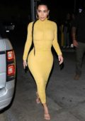 Kim Kardashian stuns in a form-fitting yellow dress as she arrives at Carousel restaurant in Glendale, California