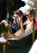 Kristin Cavallari wears a black bikini as she relaxes by the pool with husband Jay Cutler in Miami, Florida