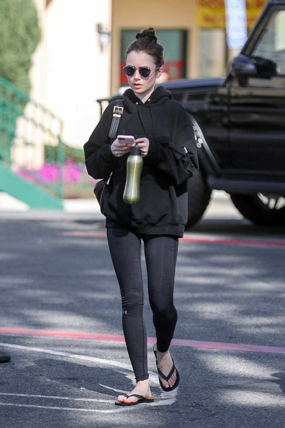 Lily Collins sports a black hoodie and leggings as she wraps up a hot pilates workout in West Hollywood, California