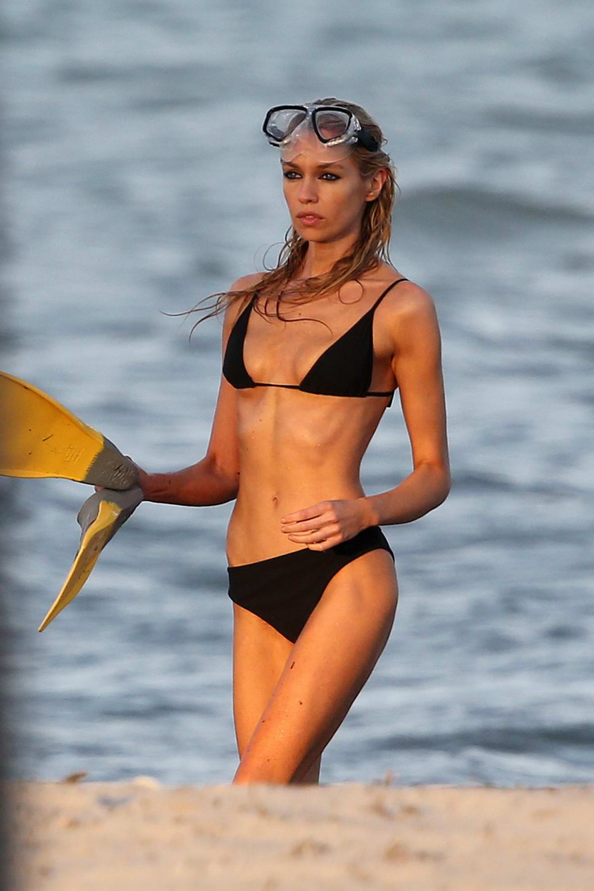 Stella Maxwell wears a black bikini as she emerges from the sea during a photoshoot in Miami, Florida