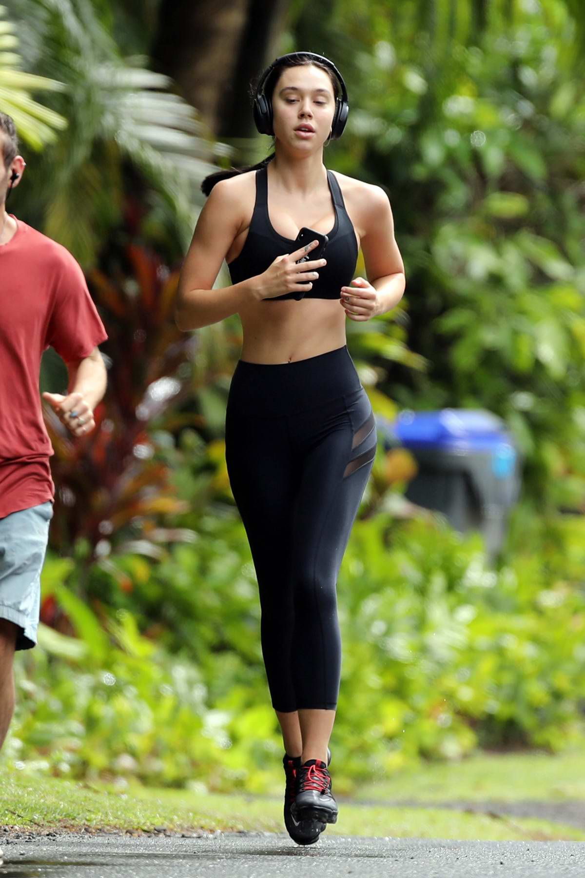 Alexis Ren shows off her amazing figure in a black crop top and leggings while out for run in Hawaii