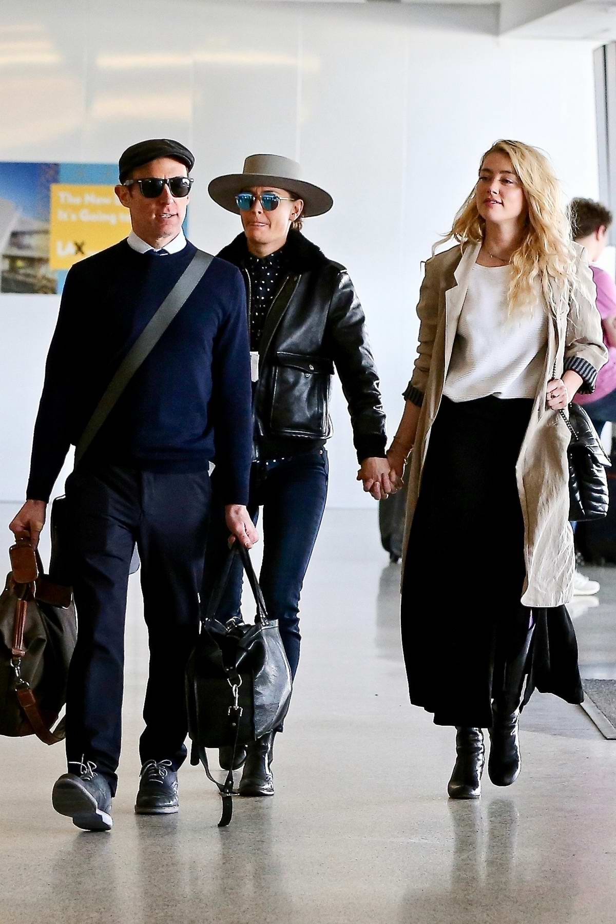 Amber Heard and girlfriend Bianca Butti walk hand in hand as they depart from LAX in Los Angeles
