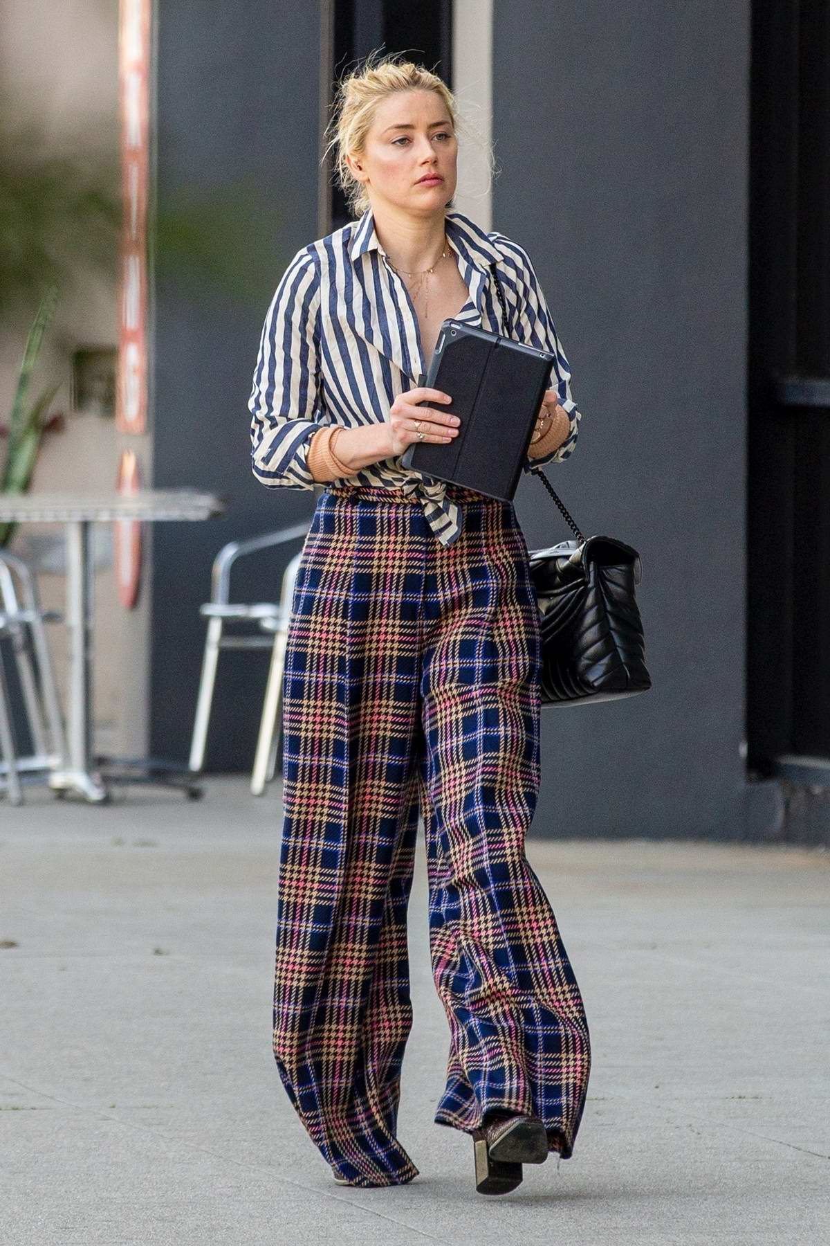 Amber Heard looks stylish in a striped shirt and plaid trousers while attending a business meeting in Beverly Hills, California