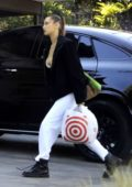 Bella Hadid wears a black fleece jacket and white sweatpants as she picks up some essentials at Target in Los Angeles