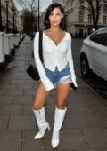 Cally Jane Beech rocks denim cut-offs with a white top and boots as she arrives at the Hangout event in Mayfair, London, UK
