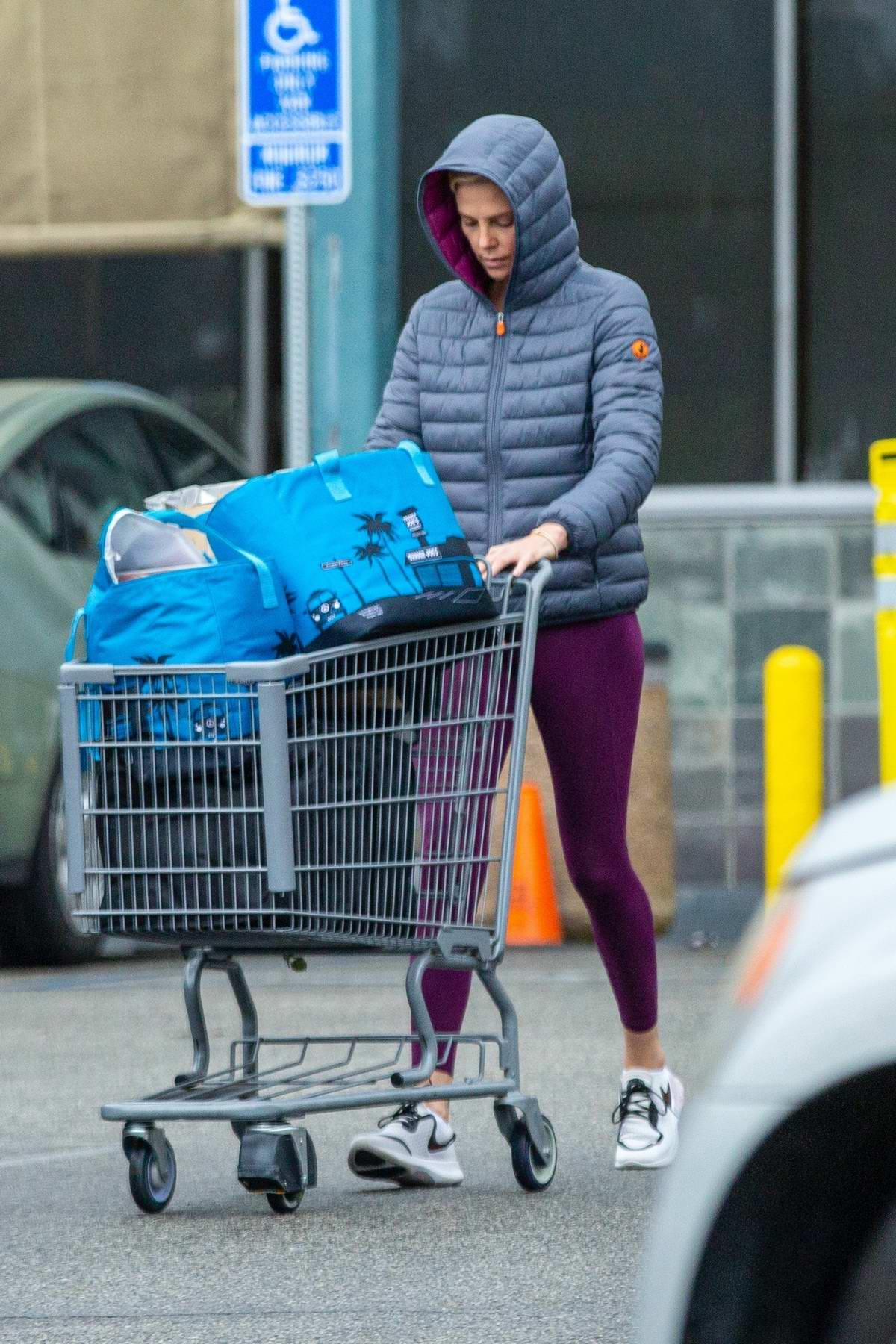 Charlize Theron looks comfy in a puffer jacket and leggings while shopping at Whole Foods on a rainy day in West Hollywood, California