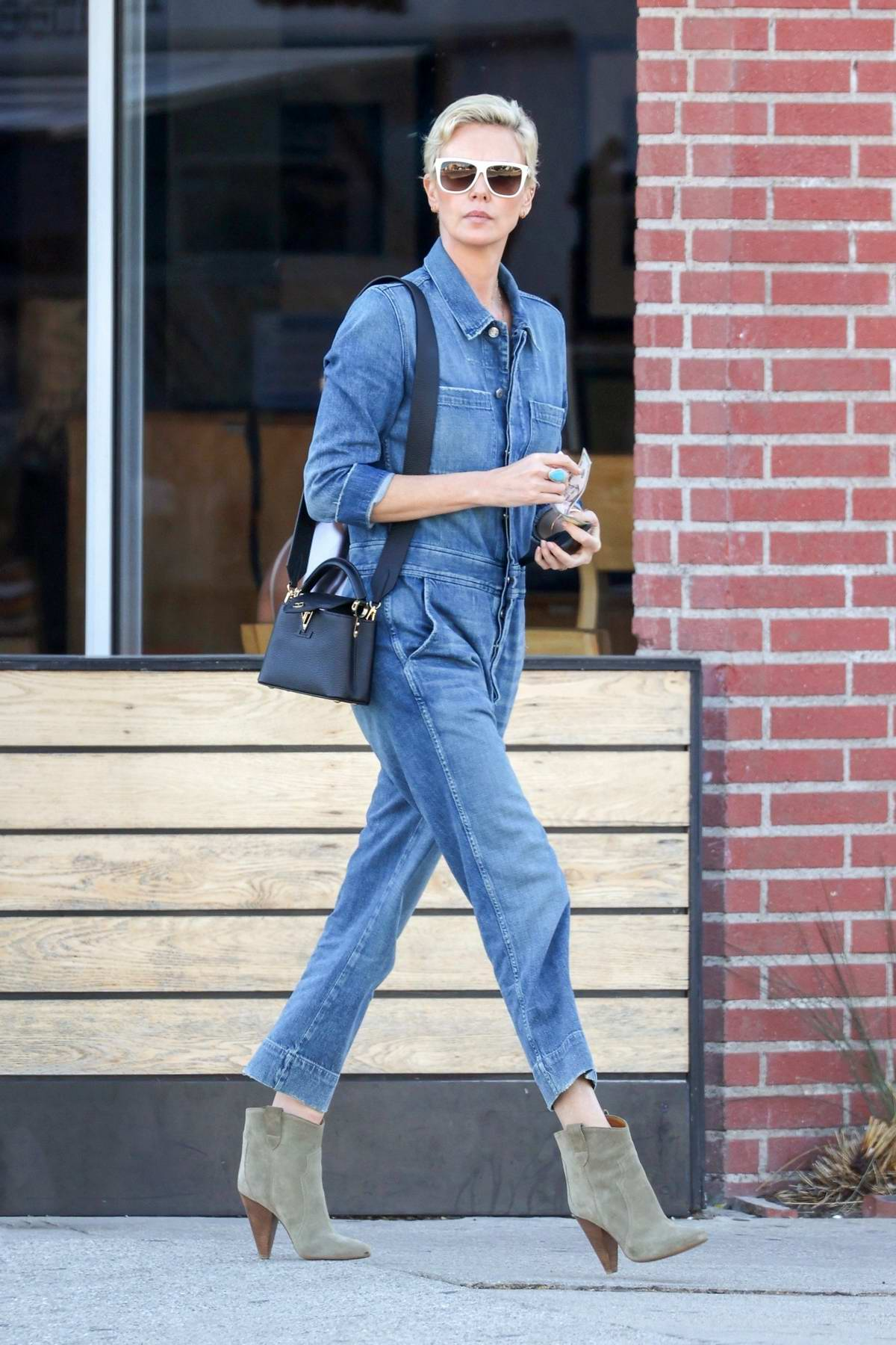 Charlize Theron rocks a denim jumpsuit and suede boots for lunch at Sugarfish in Los Angeles
