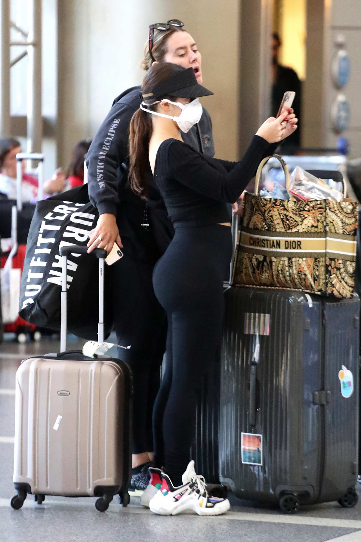 Demi Rose seen wearing a black crop top and leggings with a face mask as she jets out of LAX in Los Angeles