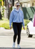Elle Fanning wears a blue hoodie and black leggings while out for a stroll with her mother in Los Angeles