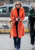 Florence Pugh steps out wearing a bright orange coat in Paris, France
