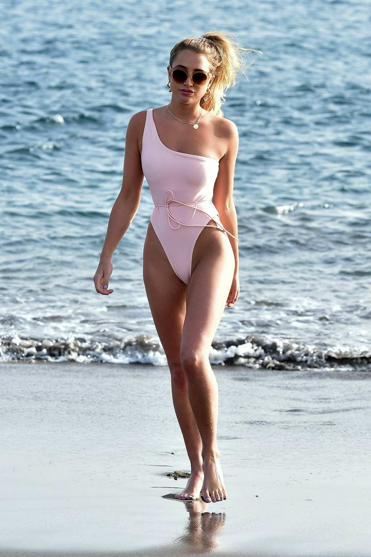 Georgia Harrison wears a light pink swimsuit while enjoying a day on the beach in Tenerife, Spain