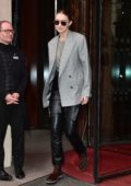 Gigi Hadid wears a grey blazer and black leather pants as she leaves Royal Monceau hotel in Paris, France