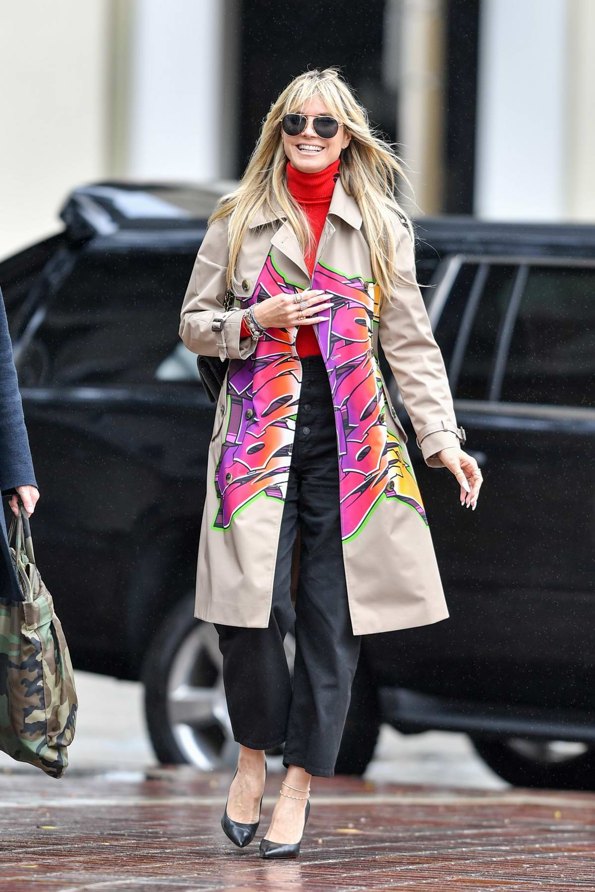 Heidi Klum dons a cool graffiti coat as she arrives at America's Got Talent in Pasadena, California