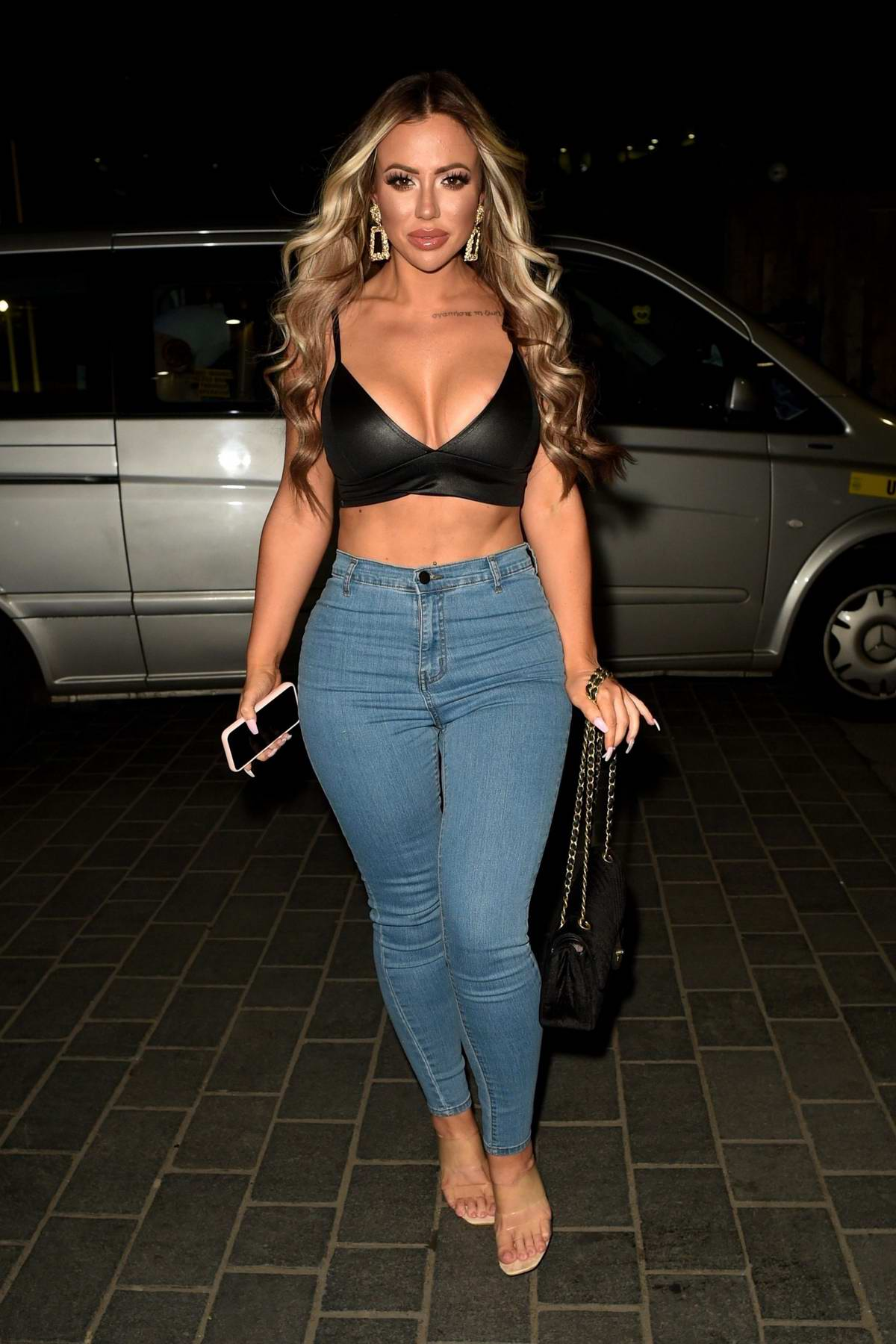 Holly Hagan wears a black crop top and jeans during a night out at BLVD in Manchester, UK