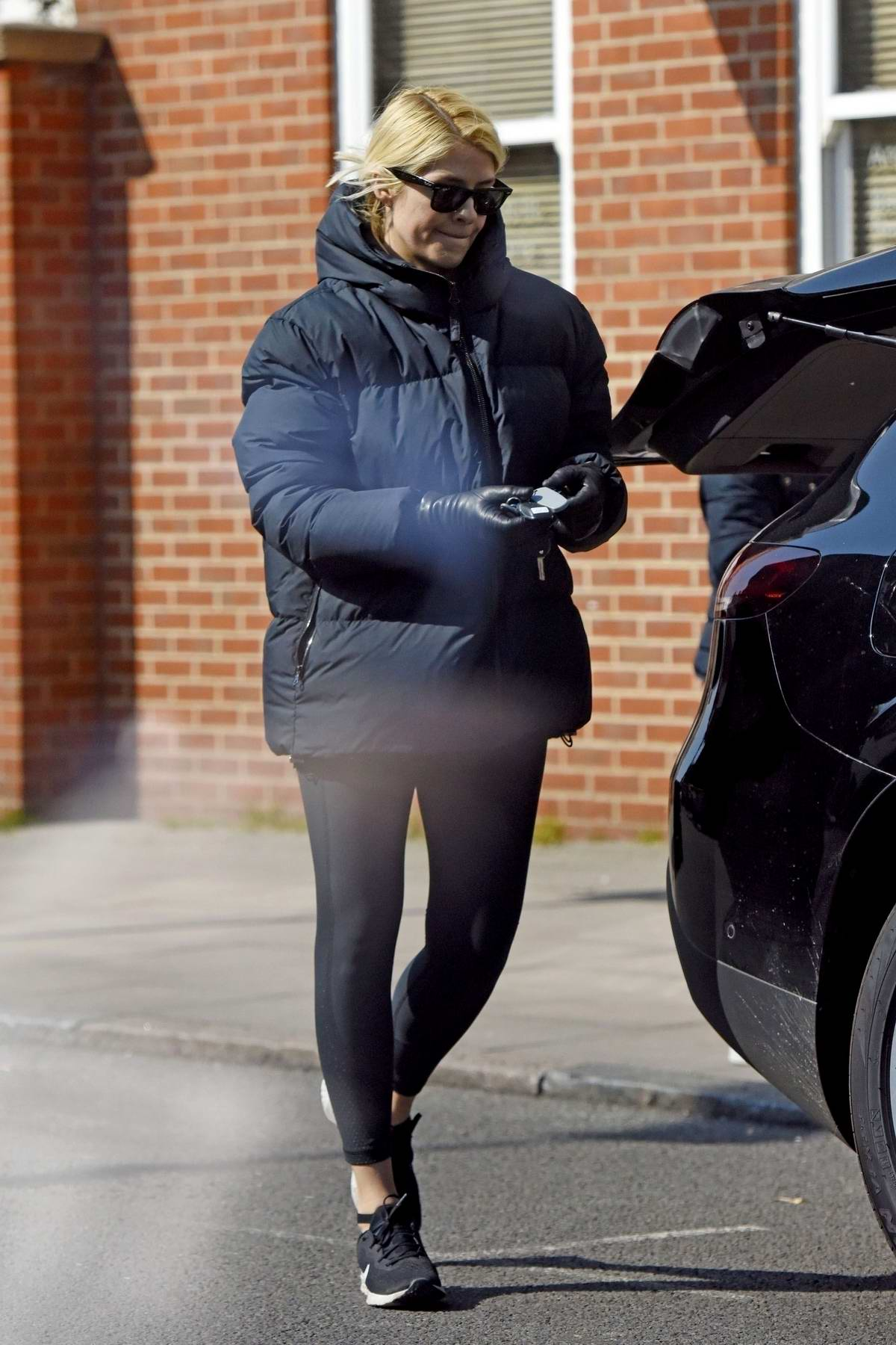Holly Willoughby sports a puffer jacket and leggings as she stops to pick up some groceries at M&S in London, UK
