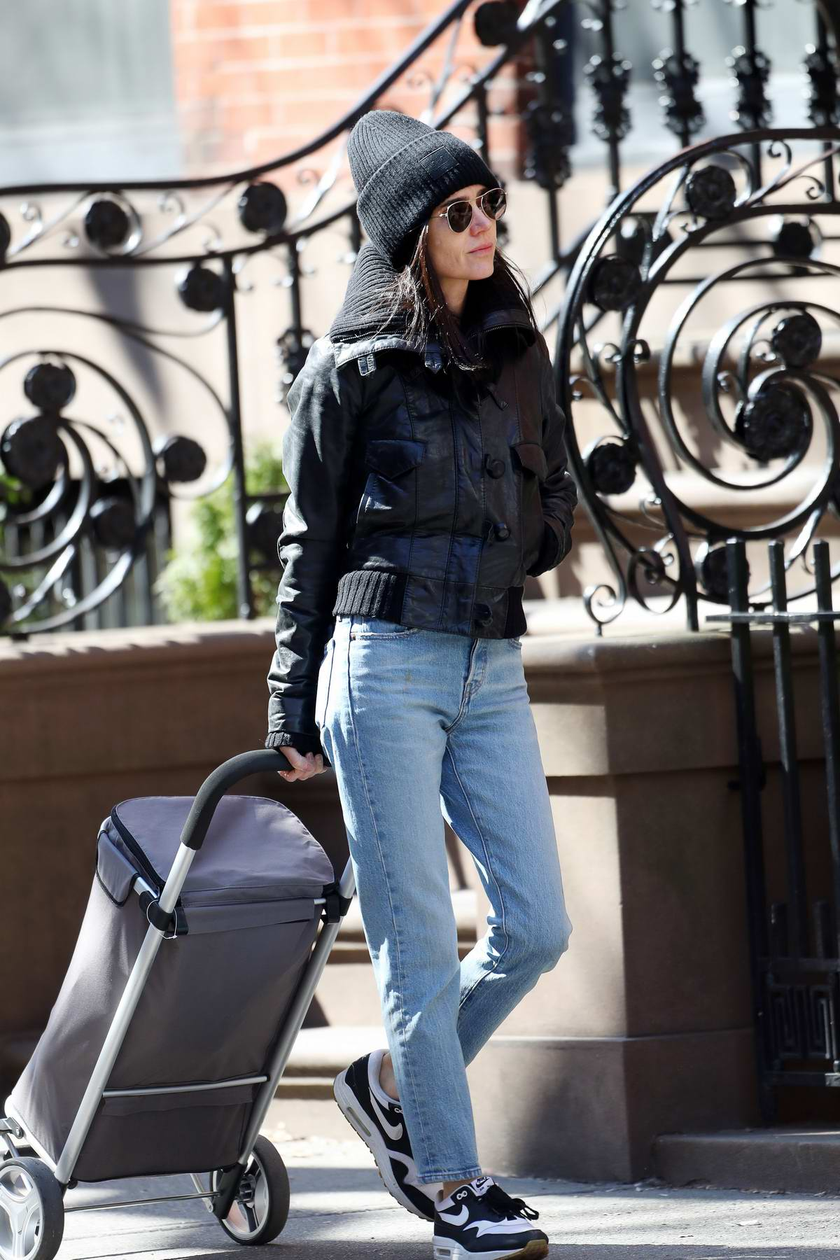 Jennifer Connelly bundles up in a black beanie, matching jacket, jeans, and Nike trainer while out in New York City