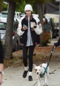 Kaia Gerber sports a beanie with a jacket and leggings while out a stroll with friends in Los Angeles
