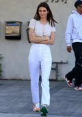 Kendall Jenner shows off her toned abs in a white crop top during a lunch outing with friends in West Hollywood, California
