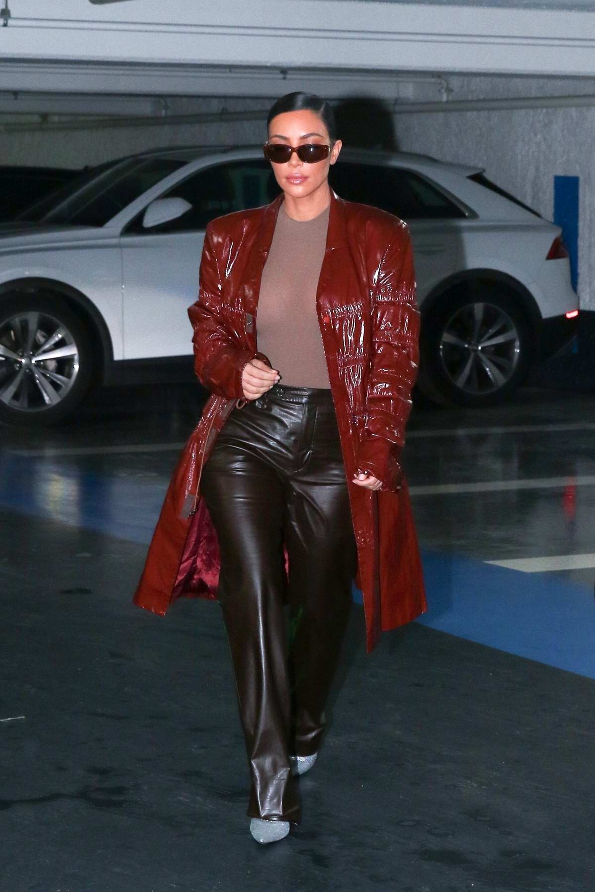 Kim Kardashian rocks a long braid and red leather coat while heading out with Kourtney Kardashian in Paris, France