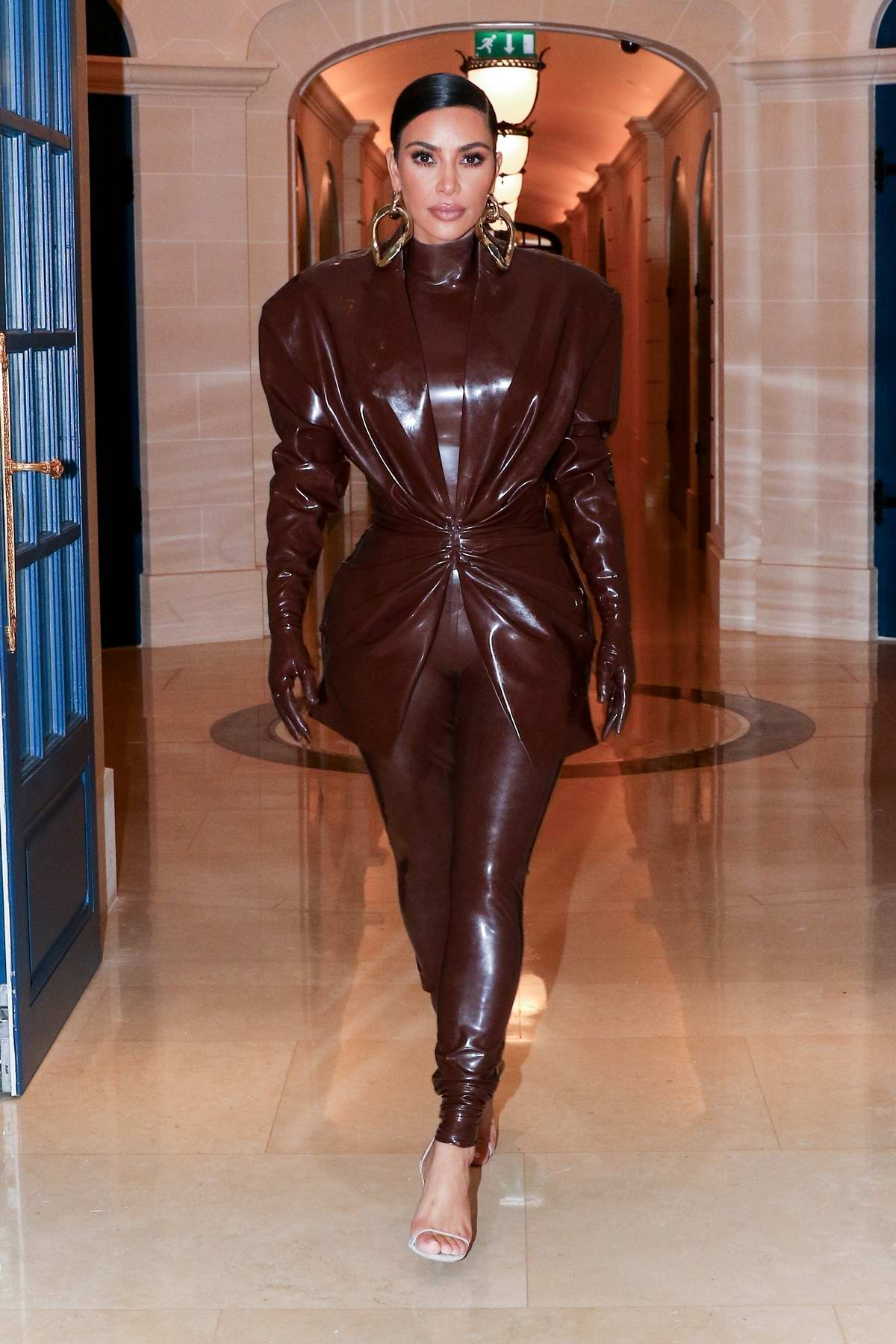 Kim Kardashian sports her second Balmain latex outfit of the day as she leaves her hotel in Paris, France