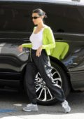 Kourtney Kardashian wears neon green sweater and black track pants for an afternoon coffee run in Studio City, California