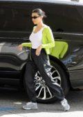 Kourtney Kardashian wears neon green sweater and black track pants for an afternoon coffee run in Studio City, California