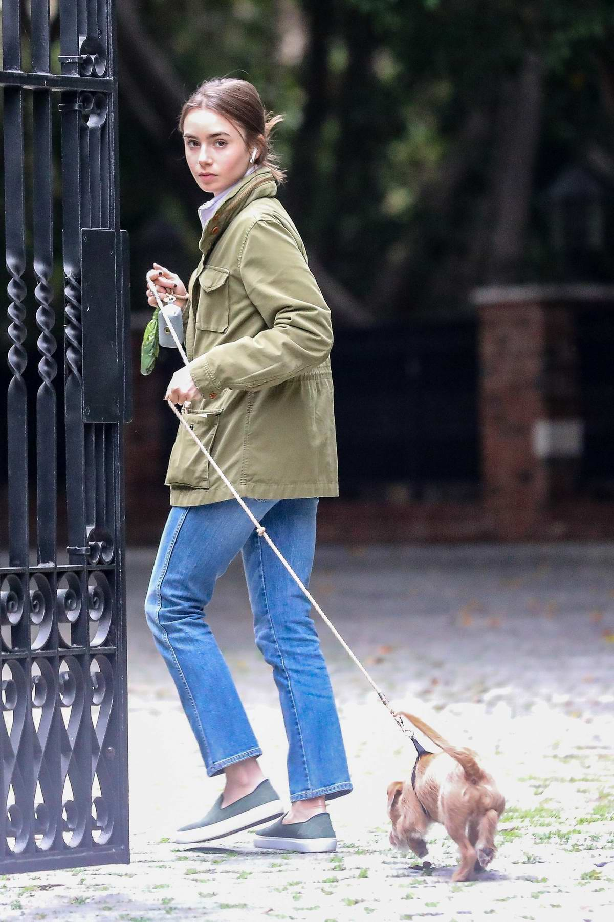 Lily Collins braves the light rain and takes her pooch for a stroll in Beverly Hills, California