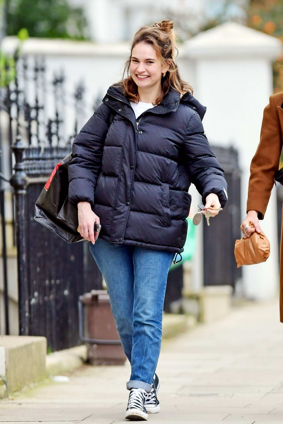 Lily James is all smiles while out for stroll with a friend in North London, UK