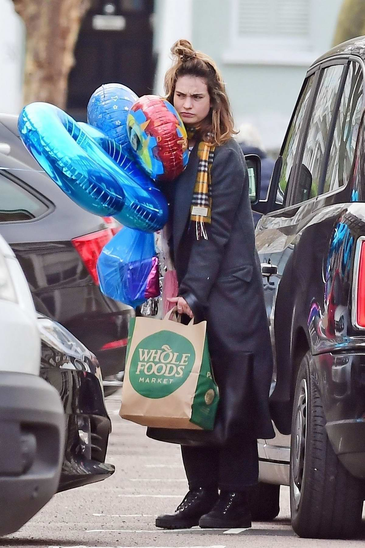 Lily James shops for birthday balloons and groceries in London, UK