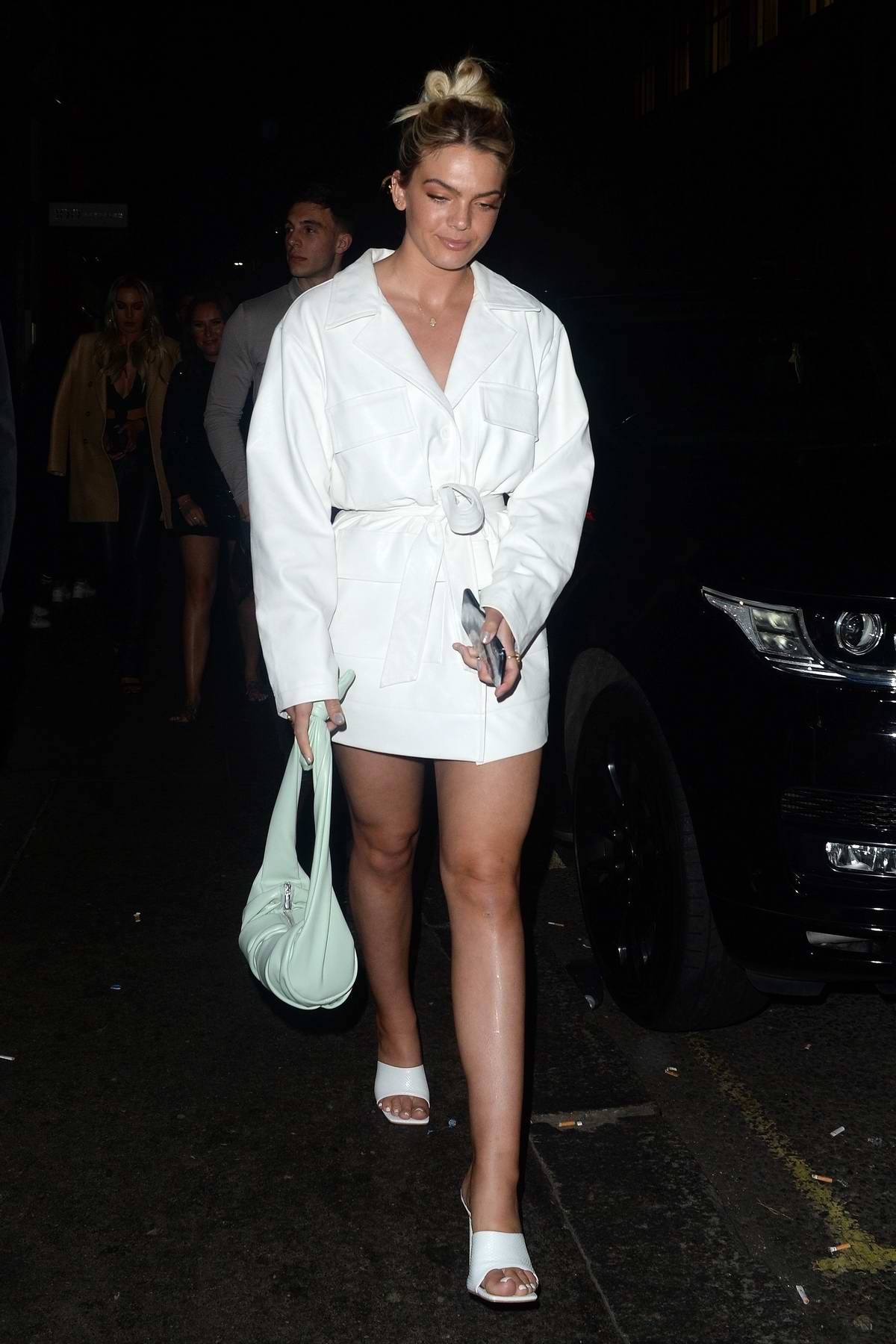 Louisa Johnson seen wearing a white mini dress as she leaves the Sintallite Party in London, UK