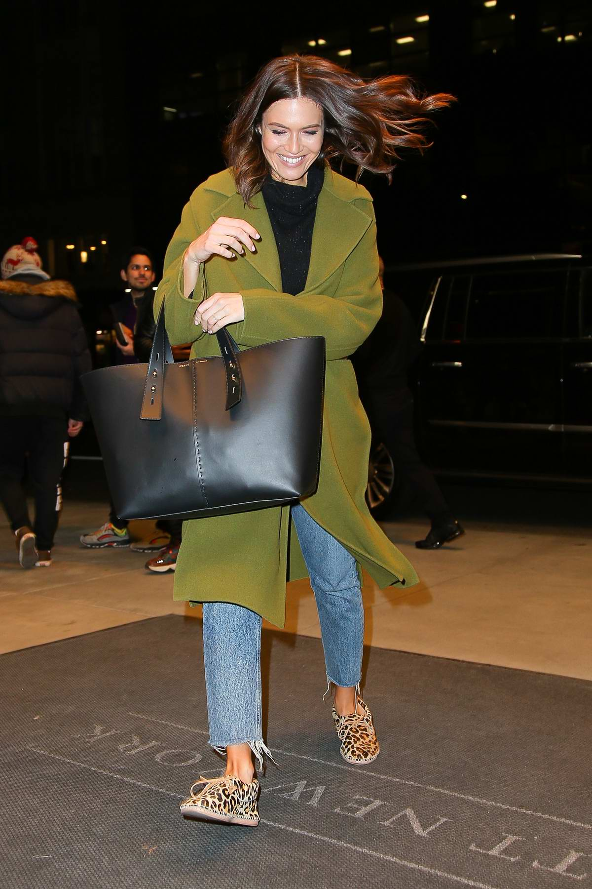Mandy Moore keeps warm in a green coat as she arrives back to her hotel in New York City