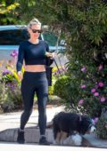 Molly Sims wears a black crop top and leggings as she takes her dog for a morning walk in Brentwood, California