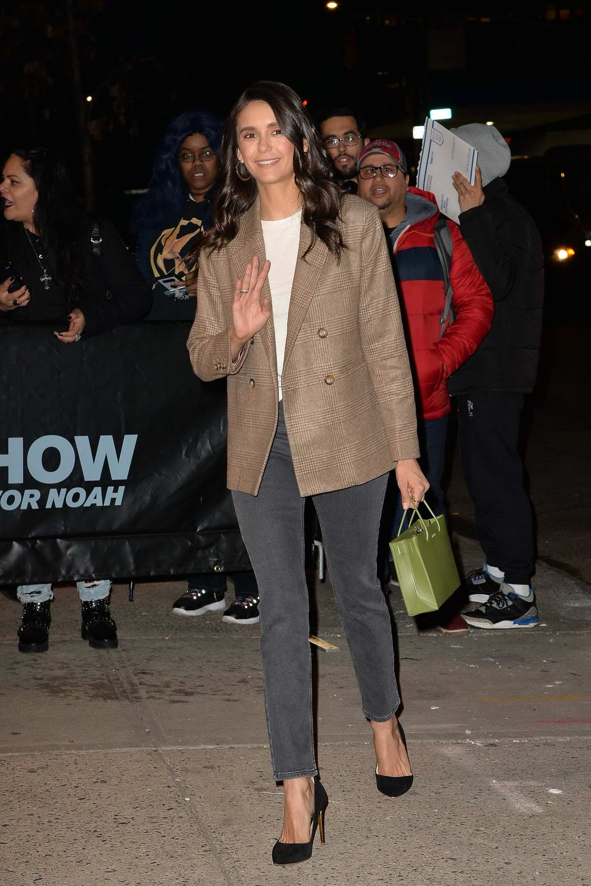 Nina Dobrev waves for the camera as she arrives at 'The Daily Show' with Trevor Noah in New York City