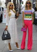 Paris and Nicky Hilton pose up for photos in colorful outfits outside Intermix women's clothing store in West Hollywood, California