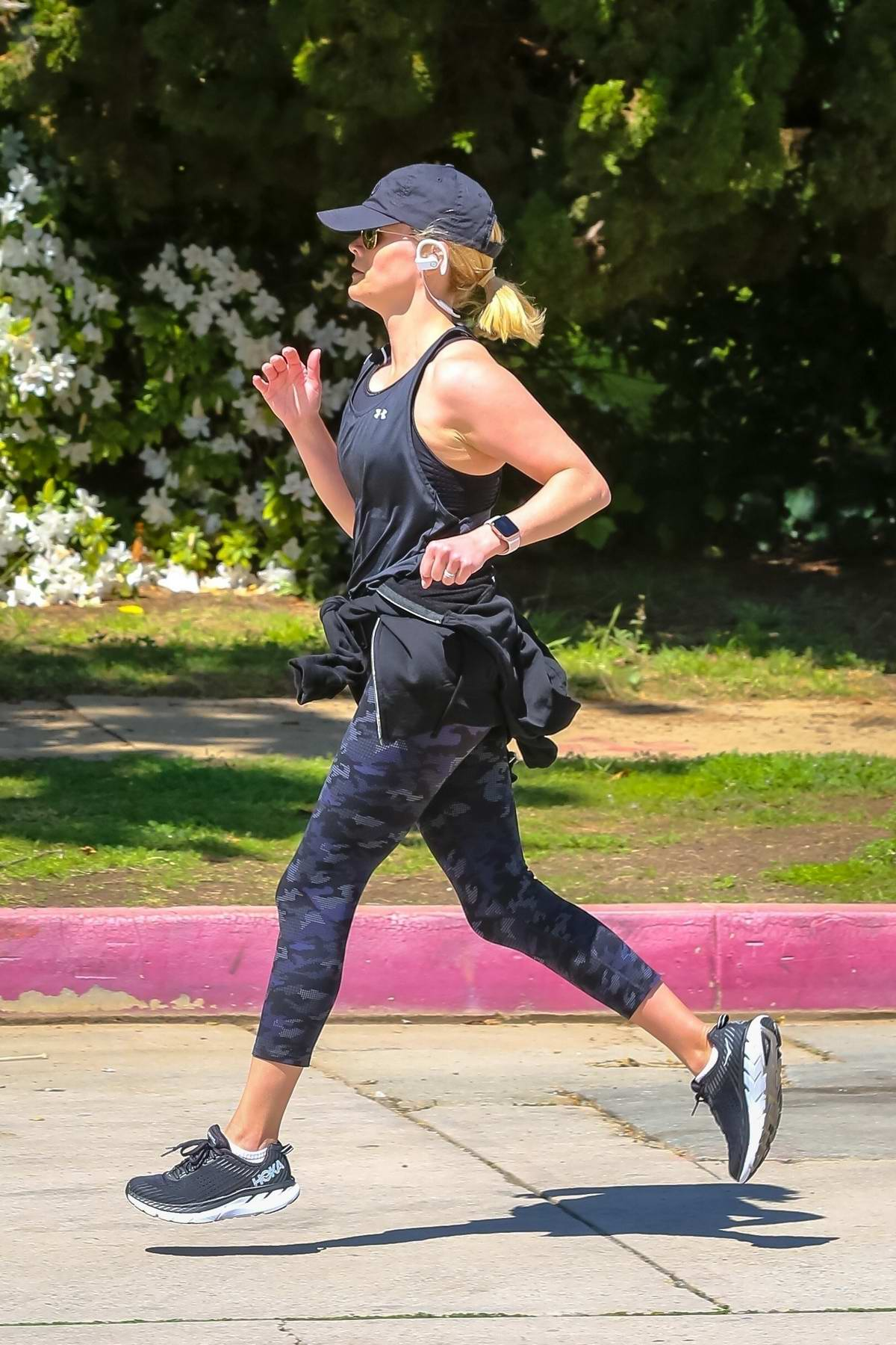 Reese Witherspoon sports a tank top and camo leggings as she goes for a jog in Brentwood, California