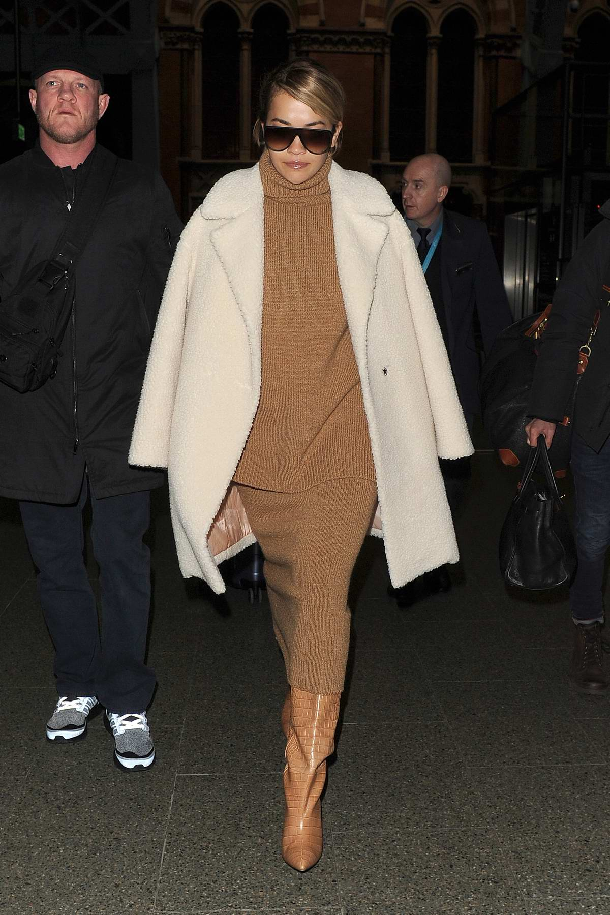 Rita Ora looks chic in a tan colored dress with a cream coat as she arrives at Kings Cross on a Eurostar train from Paris in London, UK