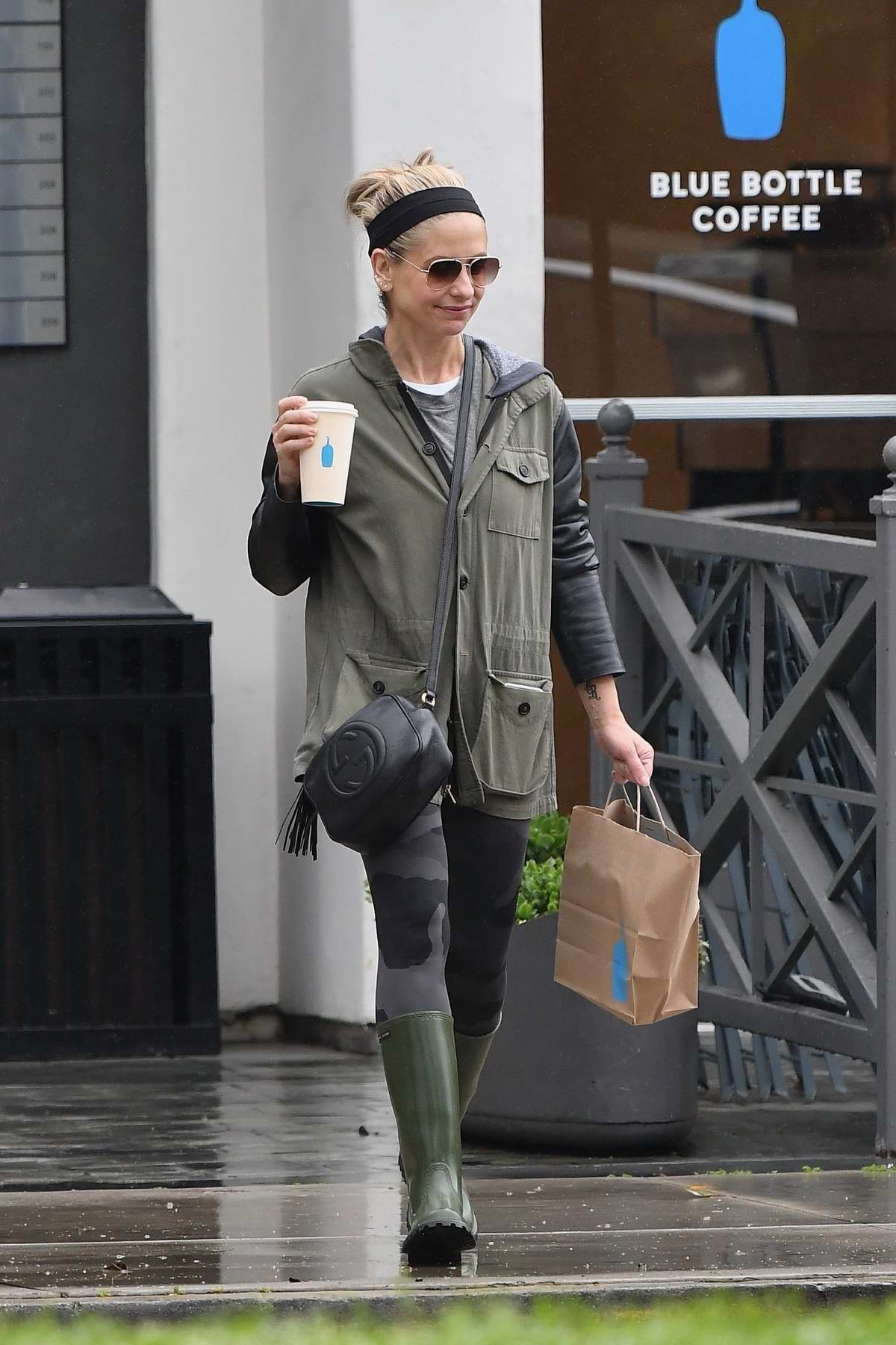 Sarah Michelle Gellar wears rain boots and leggings while grabbing a coffee on a rainy day in Brentwood, California