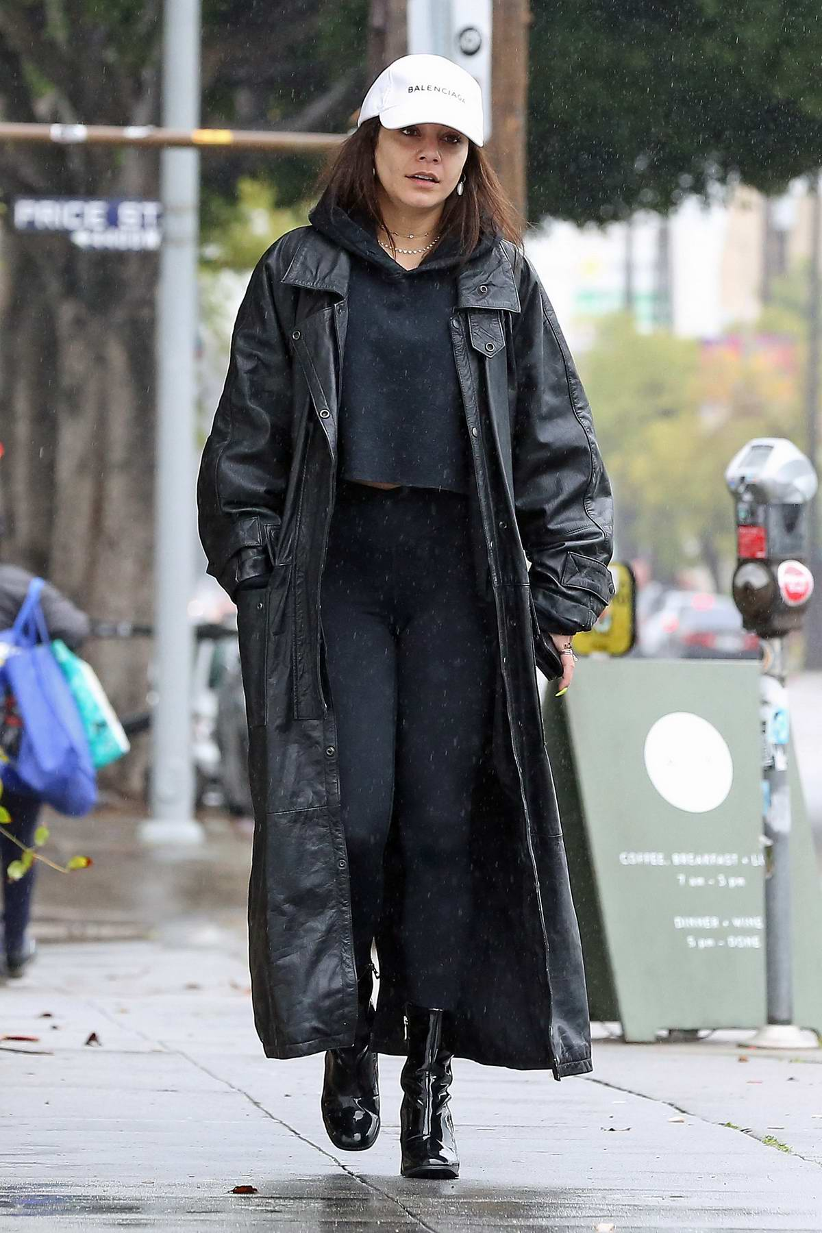 Vanessa Hudgens wears a black long coat with cropped hoodie and leggings while out in the rain in Los Angeles