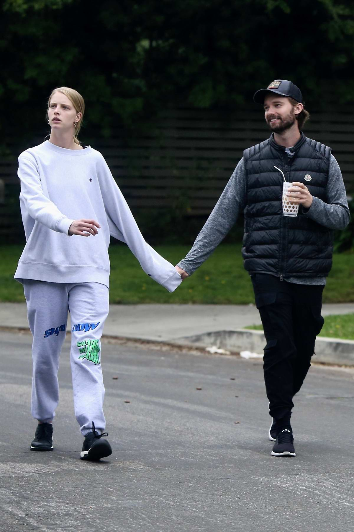 Abby Champion and Patrick Schwarzenegger hold hands as as they enjoy a walk in Brentwood, California