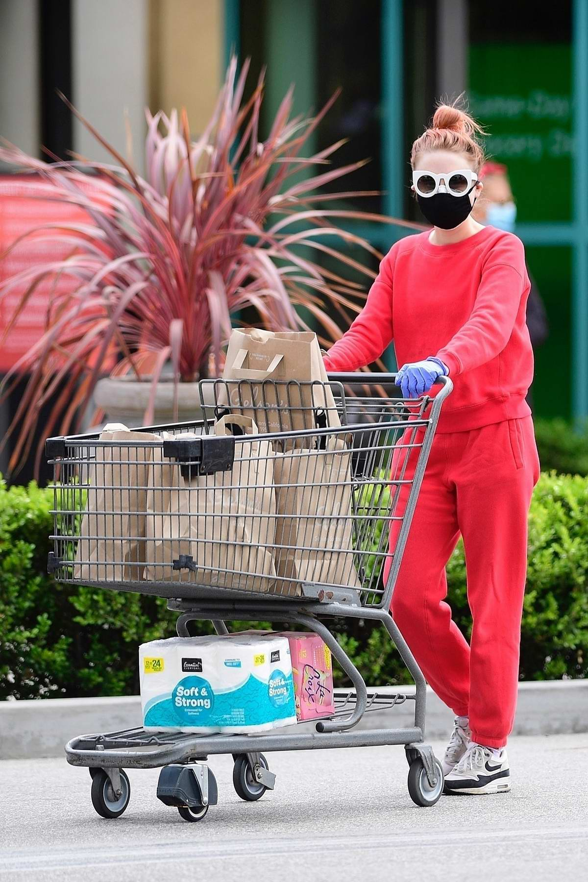 Alessandra Torresani wears red sweatsuit with protective mask, glasses and gloves during a grocery run in Los Angeles