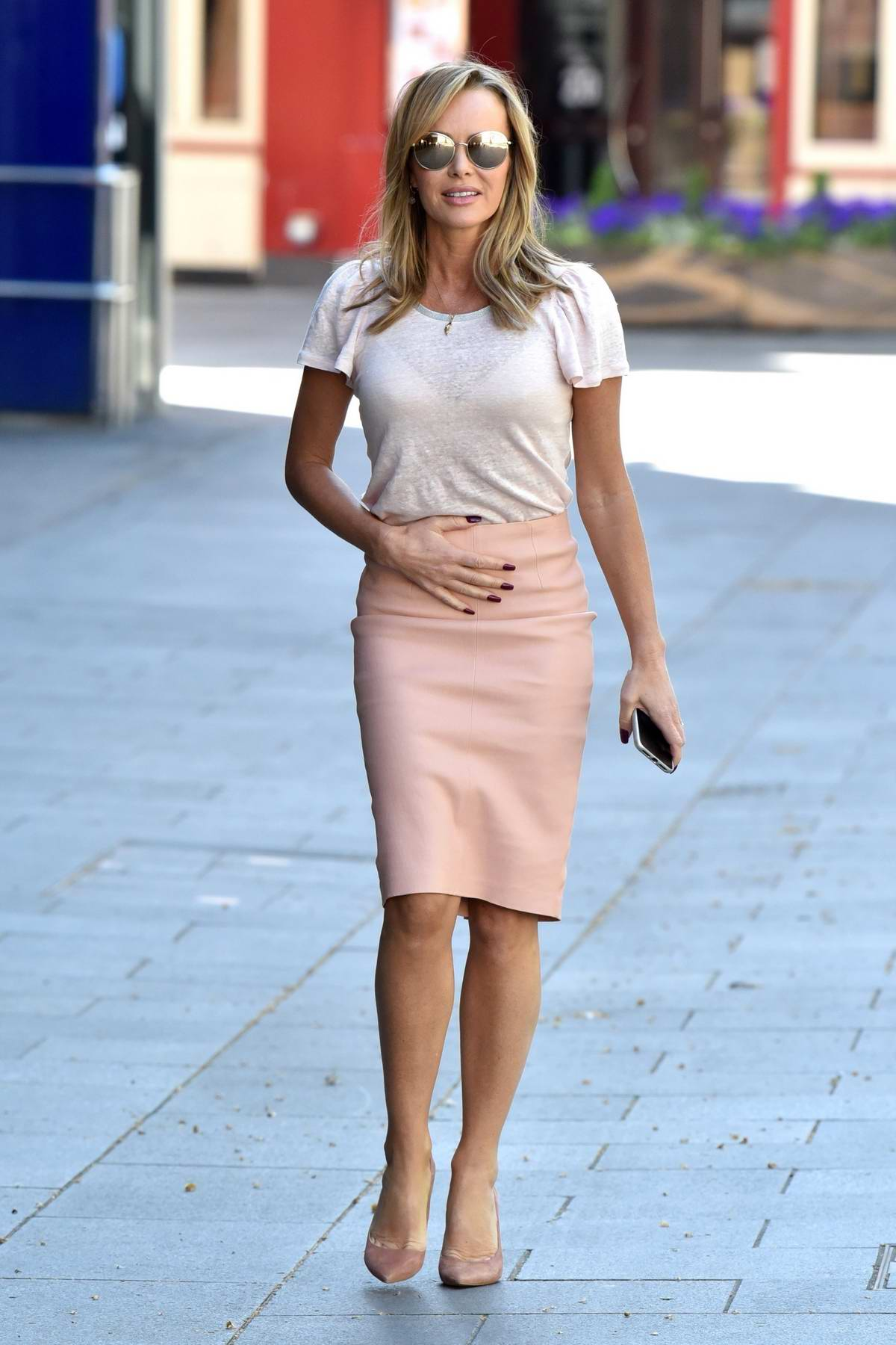 Amanda Holden seen wearing a white top and pastel pink skirt as she leaves Global Studios in London, UK