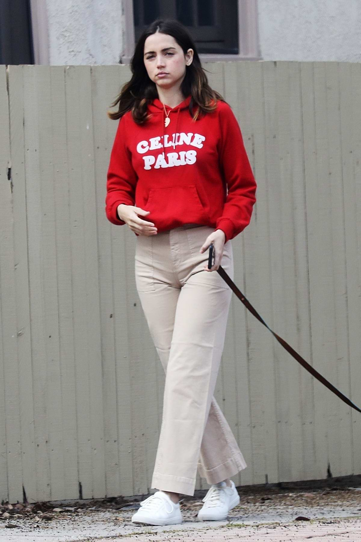 Ana de Armas dons a bright red hoodie while out for a solo stroll with her dog in the Pacific Palisades, California